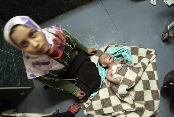 مادر بي پناه فلسطيني در كنار كودك خود كه توسط گلوله تانكهاي اسرائيل زخمي شده